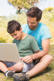 Father and son in the countryside using laptop. On a sunny day stock image