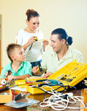 Father and son crafting with working tools, happy woman watching Royalty Free Stock Images