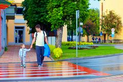 Father and son crossing the city street on crosswalk. After the rain Royalty Free Stock Photography
