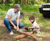 Father and the son cut wood Royalty Free Stock Image