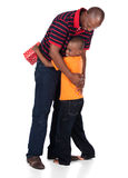Father and son. Cute african boy wearing a bright orange t-shirt and dark denim jeans is getting a gift from his father Stock Photos