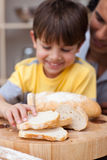 Father and son cutting bread Stock Image