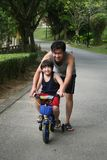Father & son cycling. Father and son cycling at the park in the evening Royalty Free Stock Photography