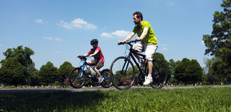 Father and son cycling in the park Royalty Free Stock Photo