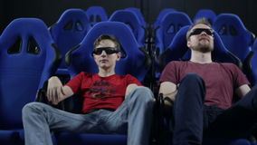 Father and son in a 5d cinema watching a movie. People in stereo glasses sit at cinema and watch movie with chair shake effects for motion imitation stock video
