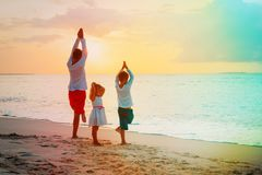 Father with son and daughter doing yoga at sunset beach. Father with son and daughter doing yoga at sunset tropical beach Royalty Free Stock Photography