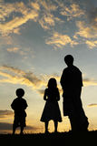 Father, son and daughter looking up. A father and his son and daughter looking up at the sky in the evening royalty free stock photography