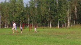 Father, son and daughter play with ball on green field with football gate at summer stock video footage