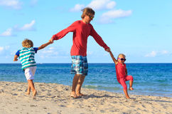 Father with son and daughter play at beach Stock Photo