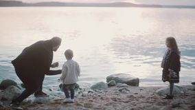 Father, son, daughter on shore. Man squatting, show to boy and girl how play stone skipping, making circles on water. stock footage