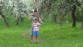 Father with son and daughter on shoulders have fun in garden. Slow motion stock video