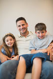 Father with son and daughter smiling on sofa. Portrait of father with son and daughter smiling while sitting on sofa royalty free stock image