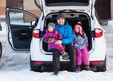 Family travel by car in winter. Father with son and daughter travel by car in winter royalty free stock photography