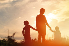 Father with son and daughter walk at sunset Stock Images