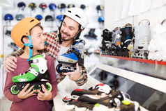 Father and son deciding on new roller-skates in sports store. Happy russian father and son deciding on new roller-skates in sports store royalty free stock image