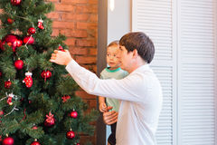 Father and son are decorating the Christmas tree Royalty Free Stock Photography