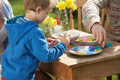 Father And Son Decorating Easter Eggs. On Table Outdoors Stock Photos