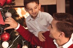 Father and son decorating tree. Happy father and son decorating Christmas tree Royalty Free Stock Photos