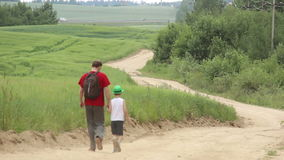 Father and son descend from the mountains near the field stock footage