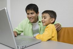 Father and Son at desk Using Laptop close up Royalty Free Stock Photography