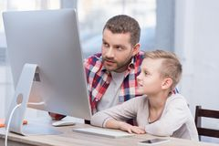 Father and son with desktop computer. Focused father and son using desktop computer together Royalty Free Stock Images
