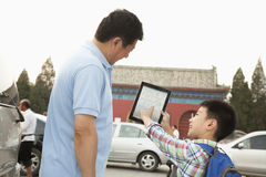 Father and son with digital tablet, son smiling and pointing, outdoors stock photos