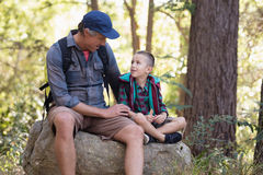 Father and son discussing while sitting on rock Royalty Free Stock Photo