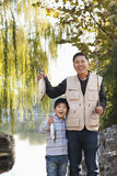 Father and son displaying fishing catch at lake stock photo