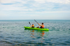 Father and son do kayaking at the lake with beautiful natural background tourists on yellow kayak boat after clean trash. Two men paddle a kayak on the sea stock photo