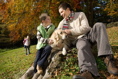 Father, son, and dog sitting on tree stump in woods Stock Photo