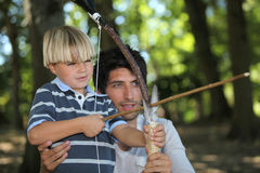 Father and son doing archery. M men and a little boy doing archery in the forest Stock Images