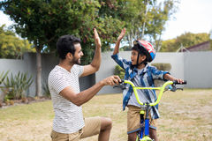 Father and son doing high five in yard Stock Photography