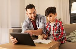 Father and son doing homework together. Education, family and homework concept - happy father and son with tablet computer writing to notebook at home royalty free stock photos