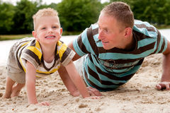 Father and son doing push-ups stock photography