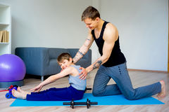 Father and son doing sit ups. Together Stock Photo