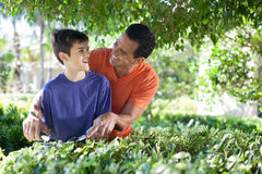 Father and son doing yard work together. Stock Photo