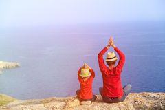 Father and son doing yoga in mountains at the sea Royalty Free Stock Photography
