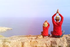 Father and son doing yoga in mountains at the sea Royalty Free Stock Photo