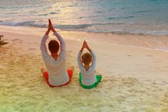 Father and son doing yoga at sunset beach. Father and son doing yoga at sunset tropical beach Royalty Free Stock Images