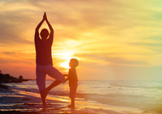 Father and son doing yoga at sunset Stock Photography