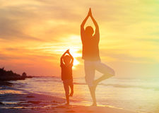 Father and son doing yoga at sunset. Sea Stock Photos