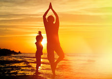 Father and son doing yoga at sunset Royalty Free Stock Image