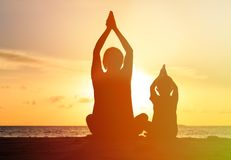 Father and son doing yoga at sunset Stock Images