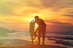 Father and son doing yoga at sunset sea stock image