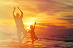 Father and son doing yoga at sunset sea Royalty Free Stock Image