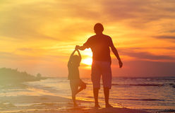 Father and son doing yoga at sunset sea Stock Photos