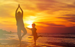 Father and son doing yoga at sunset sea Stock Images