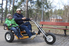 Father and son double bike ride in the park in spring Royalty Free Stock Photography