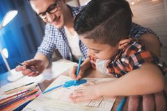 Father and son are drawing with color pencils and markers on paper at night at home. Father and son are drawing with color pencils and markers on paper at table Royalty Free Stock Photos