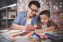 Father and son are drawing with color pencils and markers on paper at night at home. Father and son are drawing with color pencils and markers on paper at table Stock Photos